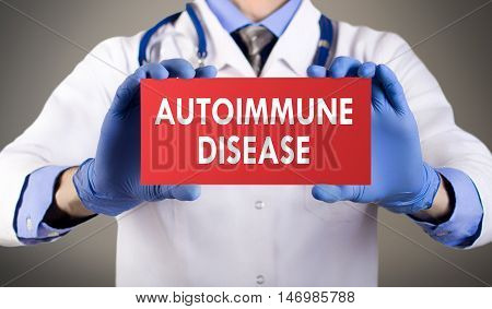 Doctor's hands in blue gloves shows the word autoimmune disease. Medical concept.