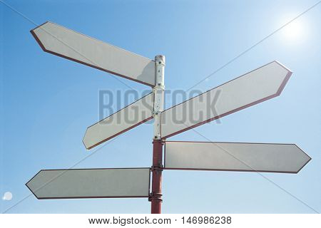 Blank sign post against blue sky
