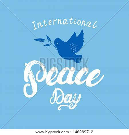 International Peace Day hand written calligraphy lettering on blue background. Peace dove with olive branch. Brush ink texture. Modern calligraphy. Vector illustration.
