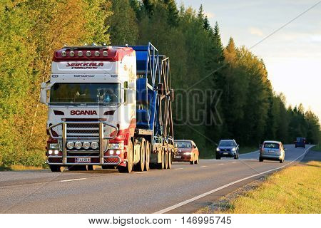 SALO, FINLAND - SEPTEMBER 9, 2016: Customized Scania semi of Seikkala Transport hauls industrial object on lowboy trailer on autumn road at sunset time.