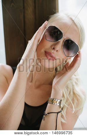 girl in sexy body posing next to a window holding her hands near the sunglasses