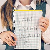 An image covering the Social Issues of child abuse schoolchild in uniform asking for help by a written message saying I am being bullied with a sad face . square format with an added instagram style filter poster