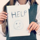 An image covering the Social Issues of child abuse schoolchild in uniform asking for help by a written message saying Help with a sad face . square format with an added instagram style filter poster