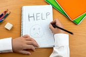 An image /poster covering the Social Issues of child abuse schoolchild in uniform at a desk asking for help by a written message saying Help with a sad face . Room for copy space and text poster