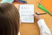 An Horizontal image / poster covering the Social Issues of child abuse schoolchild in uniform at a desk asking for help by a written message saying I am being bullied with a sad face . Room for copy space and text poster