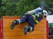 Firefighter overcomes wooden obstacle during the competition in fire sport.Contest TFA - Toughest Firefighter Alive poster