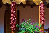 Hanging red chili peppers at a southwestern adobe style building which is a New Mexico custom taken in Santa Fe, NM poster