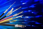 Collection of fiber optical cables on blurry technology background. Loose tubes with optical fibres and central strenght member waterblocking glass yarn and ripcord multimode or single mode poster
