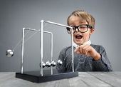 Boy doing experiment with Newton's cradle physics concept for education, action and reaction or cause and effect poster