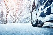 Car tires on winter road covered with snow. Vehicle on snowy alley in the morning at snowfall poster