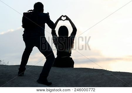Photographer Shoots A Girl With Hands In The Form Of A Heart Against The Sky