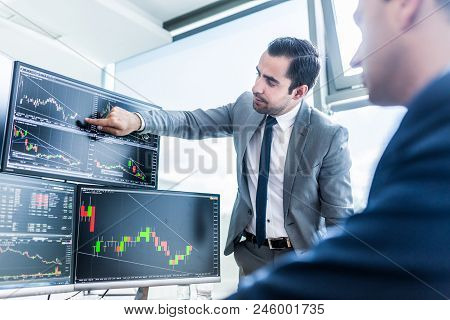 Businessmen Trading Stocks Online. Stock Brokers Looking At Graphs, Indexes And Numbers On Multiple
