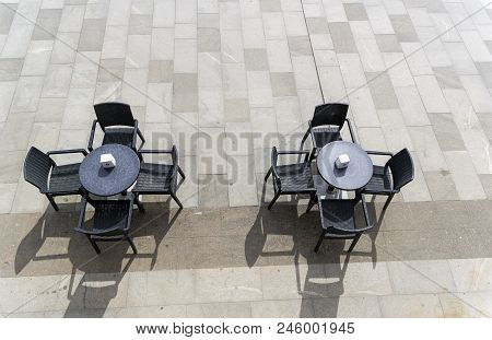 Two Unoccupied Tables In A Street Cafe. View From Above. Sunny Day.