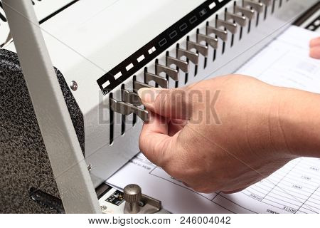 Binding documents ,Using the left hand adorned gear to penetrate the paper. Preparation for Binding poster