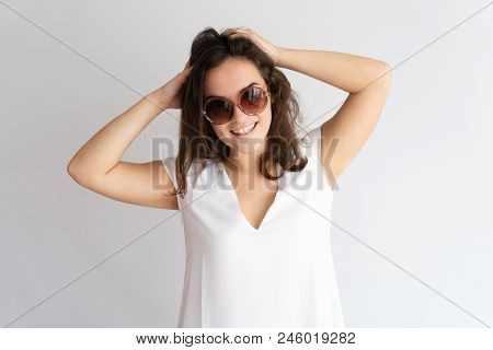Careless Beautiful Young Woman Touching Hair And Looking At Camera. Lady Wearing Summer Clothes. Sum