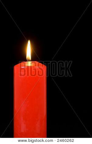 Illuminated Red Candle On Black