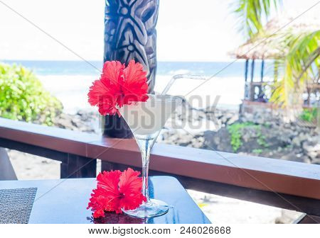 Alcoholic Cocktail Drink With Red Hibiscus Flower Garnish With Wooden Carving In Background At Beach