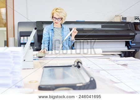 Pretty Young Woman In Glasses Using Plotter To Print Draft While Working In Printing Office.