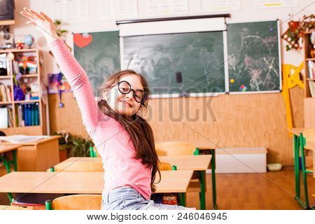 Cute Schoolgirl In Funny Big Glasses, Sitting On The Desktop And Smiling