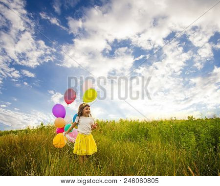 Girl With Ballons Against Blue Sky, Child Having Fun In Field Against Blue Sky Background. Freedom C