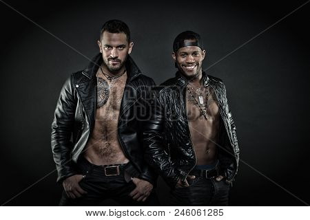 Leather masculine clothing concept. Men on smiling faces with bristle. Machos with muscular torsos look attractive in leather jackets, dark background. Men with sexy muscular torsos look brutally. poster