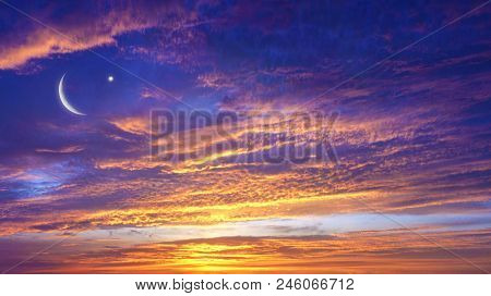 Crescent Moon With Beautiful Sunset Background .  Light From Sky . Religion Background . Red Sunset