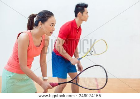Side view of a beautiful and competitive Chinese woman holding the racquet while looking forward with concentration during a squash game with her partner