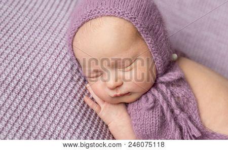 Cute little girl in purple knitted bonnet sleeping on her side