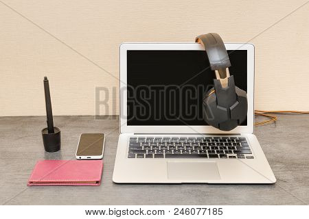 Open Laptop, Headphones, Smartphone And Notepad. Workplace Preparation