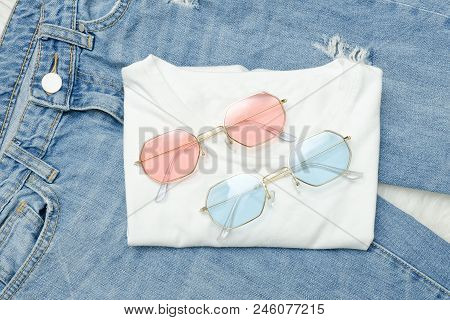 Multicolored Sunglasses On A White T-shirt And Jeans. Fashionable Concept