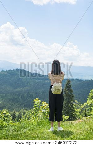 Girl With A Backpack Standing Background Of Mountains And Forests. Back View. Sunny Summer Day