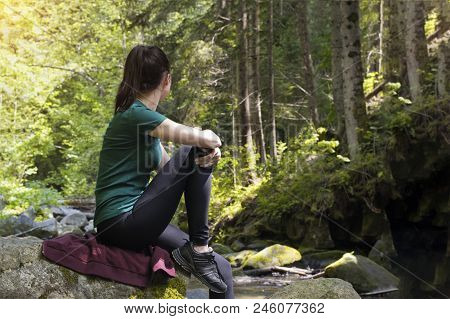 Thoughtful Girl Sits On A Rock In The Forest. Summer Day