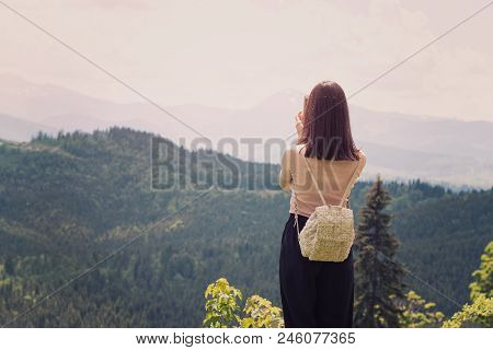 Girl With A Backpack On A Smartphone Photographs Of Mountains And Forest. Back View. Sunny Summer Da