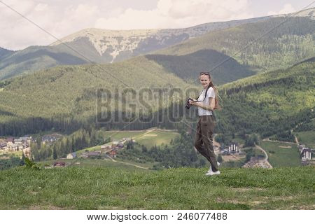 Girl With A Displeased Face And Camera Standing On A Background Of Mountains. Forest On Background