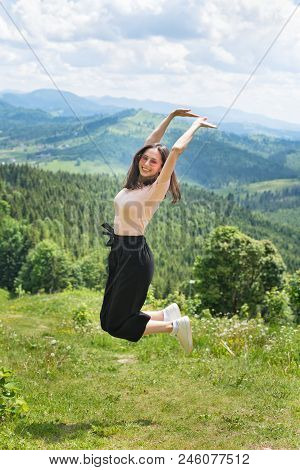 Cute Laughing Girl Is Jumping Against The Backdrop Of Mountains And Forests. Sunny Summer Day