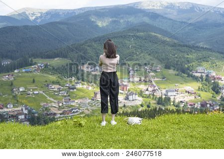 Girl Admires The Village In The Valley. Mountains In The Distance. Back View
