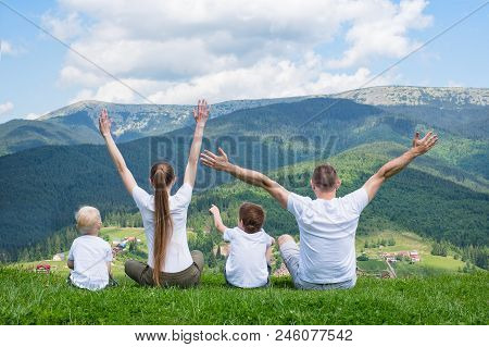 Family Holiday. Parents And Two Sons Are Sitting With Their Hands Up. View Of The Mountains. Back Vi