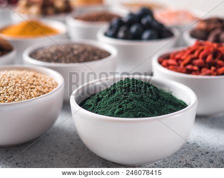 Spirulina Powder In Small White Bowl And Other Superfoods On Background. Selective Focus. Different