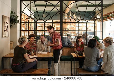 Smiling Young Waiter Taking Orders From A Diverse Group Of Customers Sitting Together At A Restauran