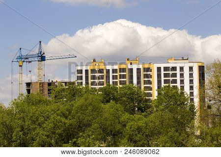 Urban View Of Silhouettes Of Two High Industrial Tower Cranes Above Green Tree Tops Working At Const