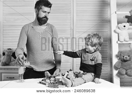 Boy Points At Mans Creation On Wooden Wall Background. Dad And Kid Build Of Plastic Blocks. Family A