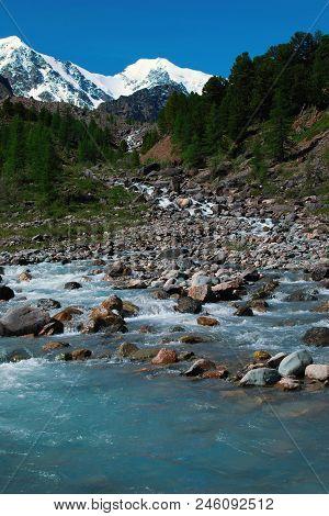 Mountain River On The Background Of Snow-capped Mountain Peaks, Blue Sky And Green Forest. Clear Wea