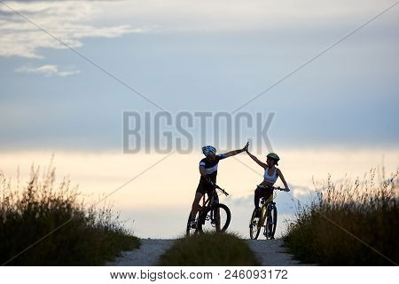 Sporty Woman And Man Wearing Sportswear And Helmets, Riding Bicycles, Having Fun Outside. Silhouette