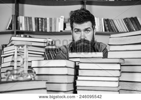 Man On Calm Face Between Piles Of Books, While Studying In Library, Bookshelves On Background. Bibli