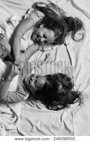 Schoolgirls In Pajamas Wallow On Colorful Pillows, Top View. Kids With Happy Faces Have Fun Lying In