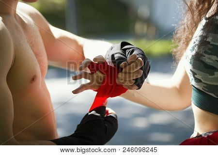 Hands Of Young Man And Woman Wrapping Hands With Bandages For Workout In Summer Day, Horizontal