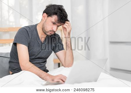 Portrait Of Heavy-hearted Man Looking On Laptop Computer In Bedroom While Massaging His Head. Misera