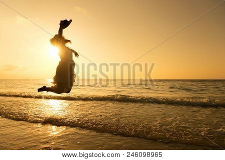 Silhouette Of Pretty Woman Wear White Dress Is Jumping And Relax On Beach. Positive Emotions. Summer