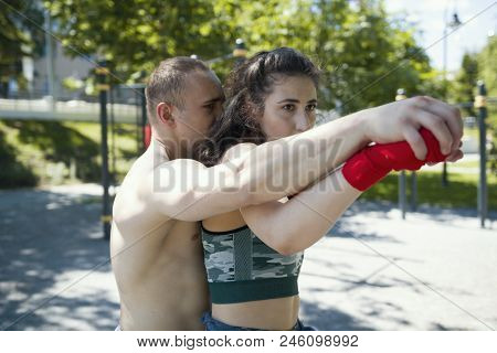 Portrait Of Young Man Holding Woman From Behind, Posing A Boxing Punch, Horizontal
