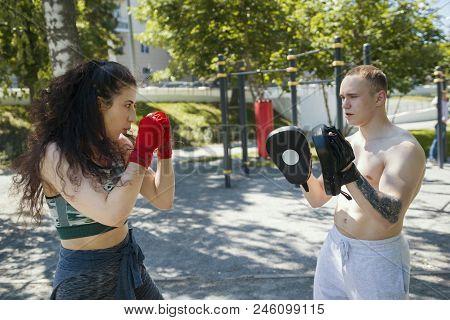 Young Man Teaches Beautiful Woman Boxing Blows Outdoors At Sunny Day, Horizontal
